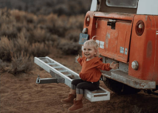 little girl sitting on the back bumper of a car, hands outstretched looking happy