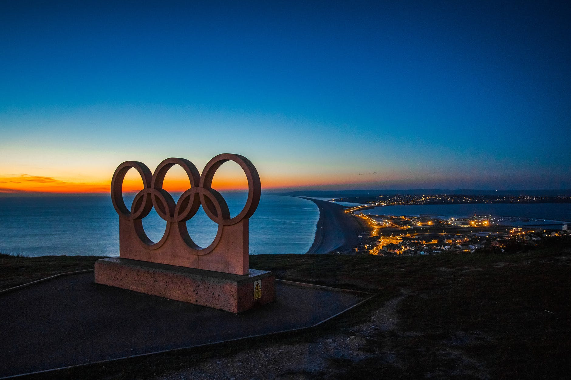 5 Olympic Rings with a lit up city in the background