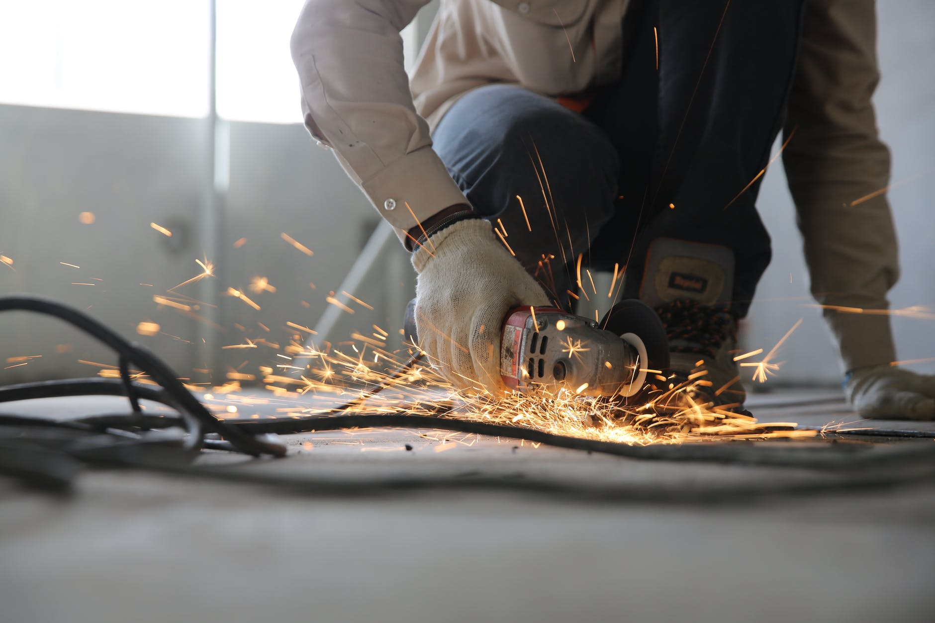 a worker using a electric saw, which has got sparks flying around it, chopping into wood