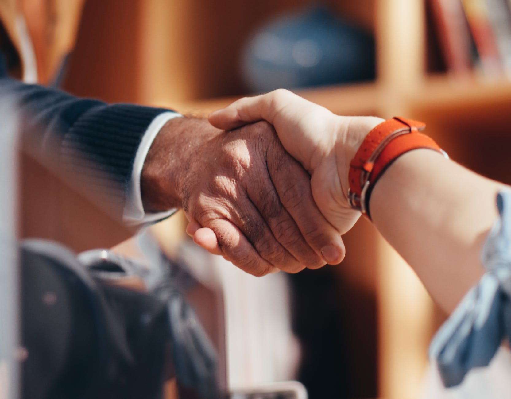 a man and a women shaking hands, one in a business suit, one looking more informal. just a close up of the hands shaking