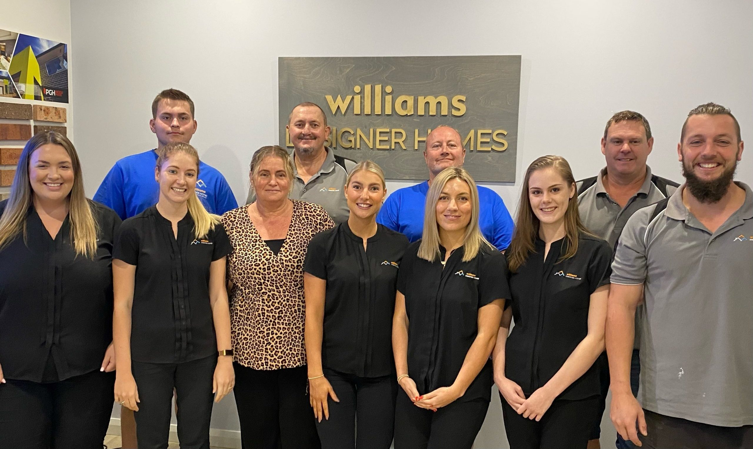 William Designer Homes team in front of an office wall with plaque behind them