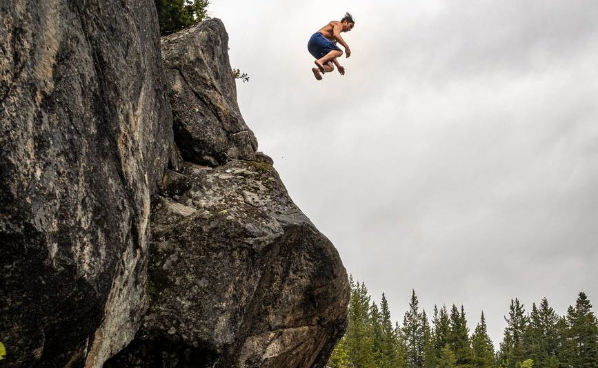 man jumping off a rock cliff into water below.
