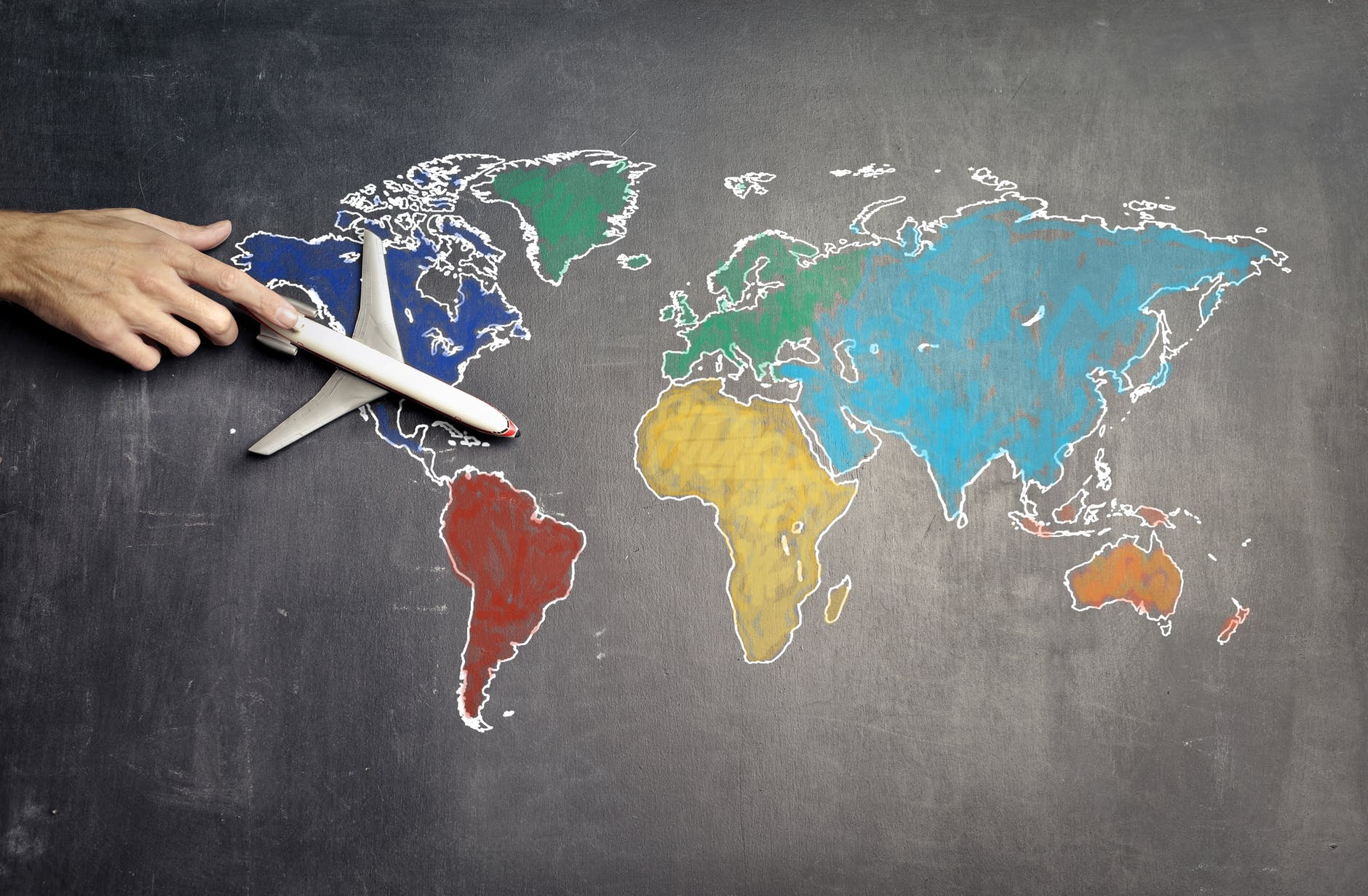 someone holding a toy aeroplane on top of a chalk created world map