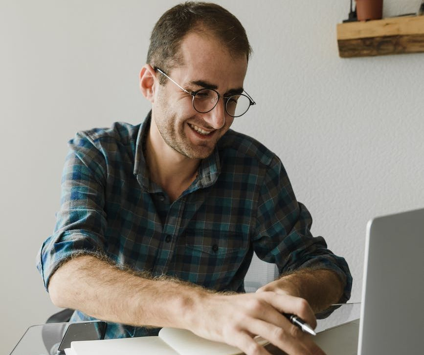 man typing on computer with his workbook open. Pen is in his left hand whilst typing