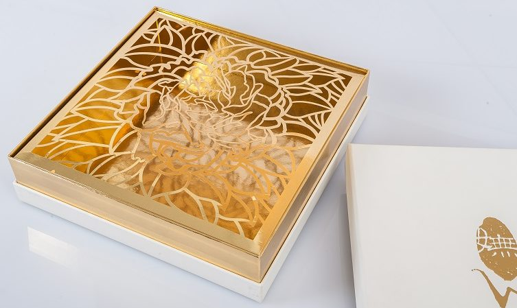 gold box sitting on top of its packaging with floral design