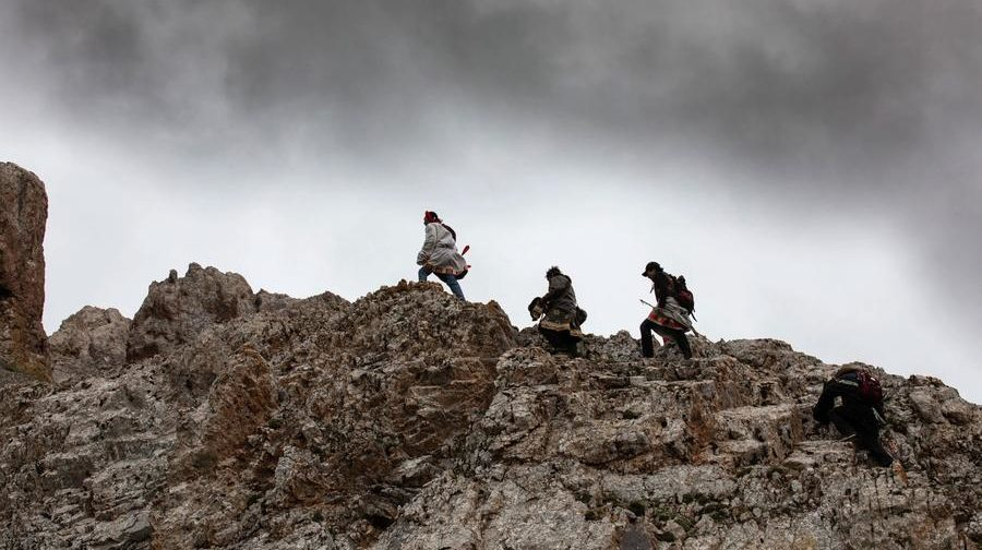 3 men walking on top of a rocky formation