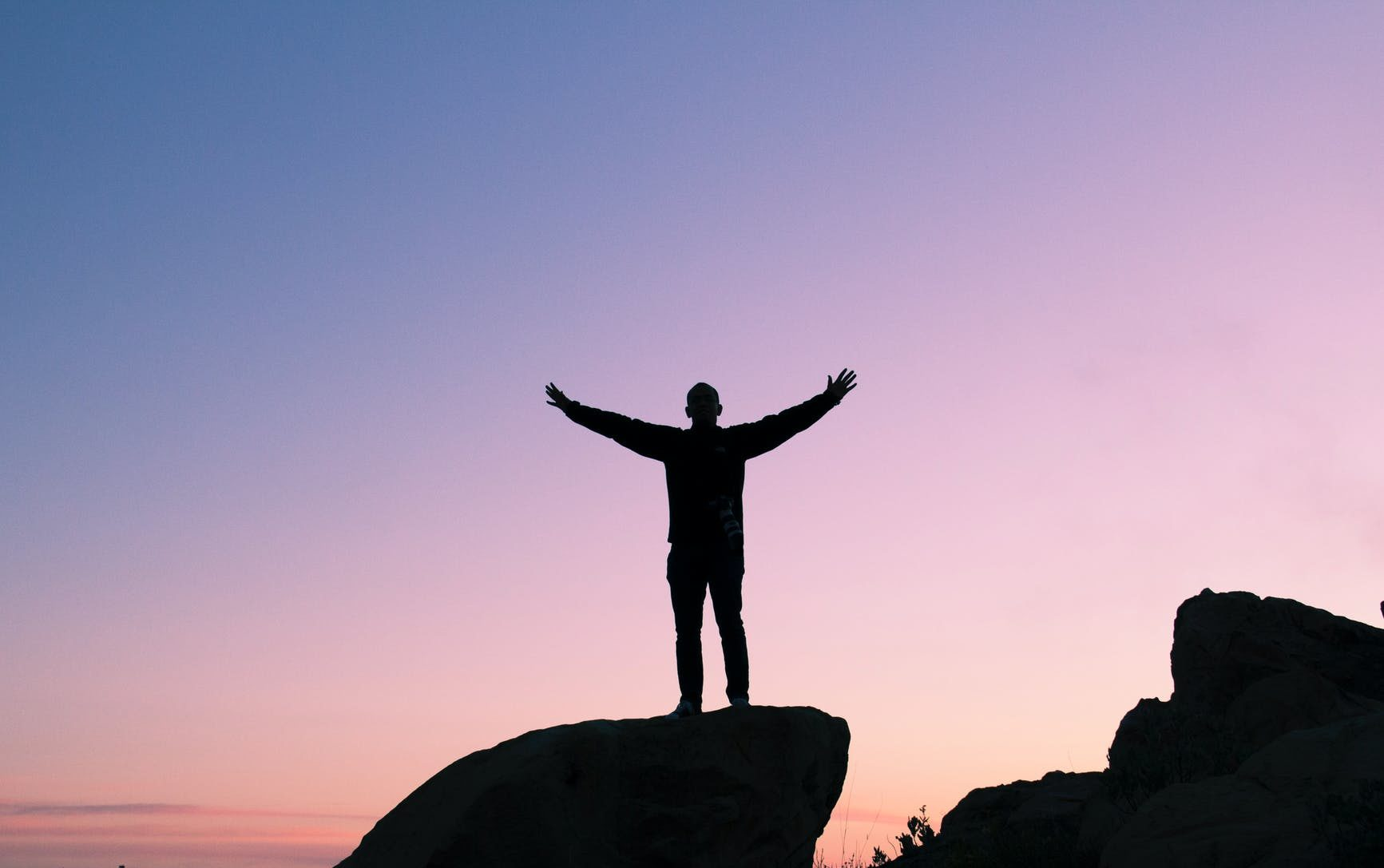 man standing on a rock with his arms outstretched to the sides in front of a sunset