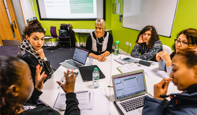 6 women sitting around a table, with laptops open, discussing meeting