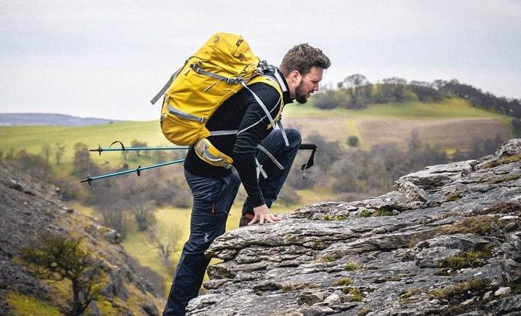 man with hiking sticks climbing up a mountain with a yellow rucksack on his back