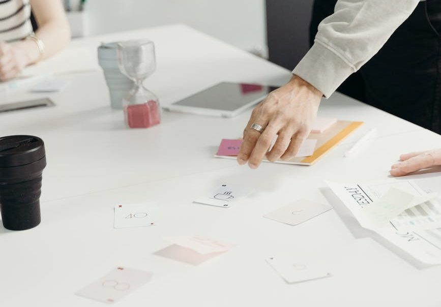 cards on a table looking to be planning, with mans hand moving them around on the table.